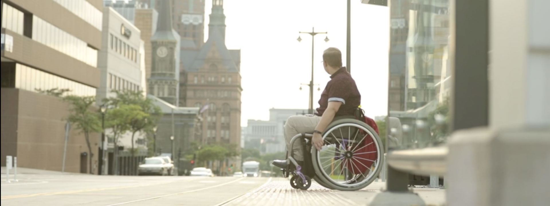 Photo of man crossing a street in a wheelchair