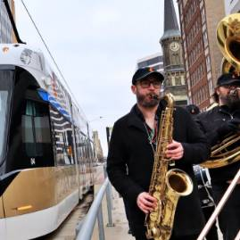 Musicians performing in front of a streetcar