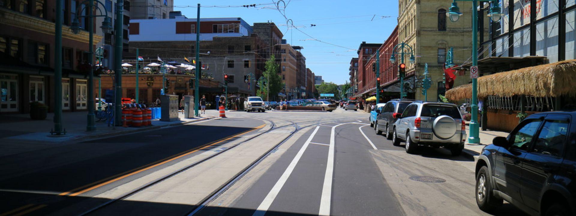 Cars parked near a streetcar's tracks